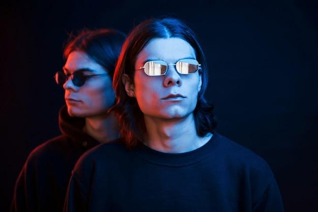 Vergelijkbare kleding. portret van tweelingbroers. studio opname in donkere studio met neonlicht