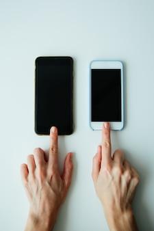 Vergelijking van twee telefoons, bovenaanzicht, kippen druk op de knoppen van de telefoons