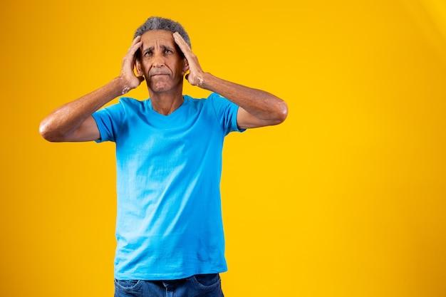 Vergeten en verwarde oudere afro man op gele achtergrond.