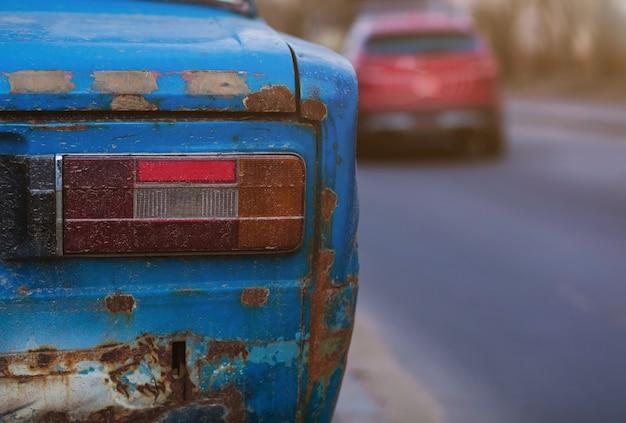 Vergeten roestige auto op weg. verlaten roestige oude auto op weg. achterlichten