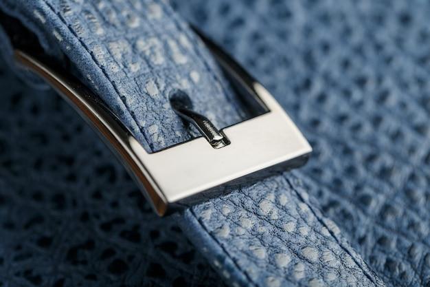 Vergrendel en gesp close-up, elementen van een blauwe rugzak gemaakt van echt leer op donker