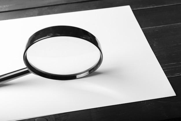 Vergrootglas en blanco papier op houten tafel