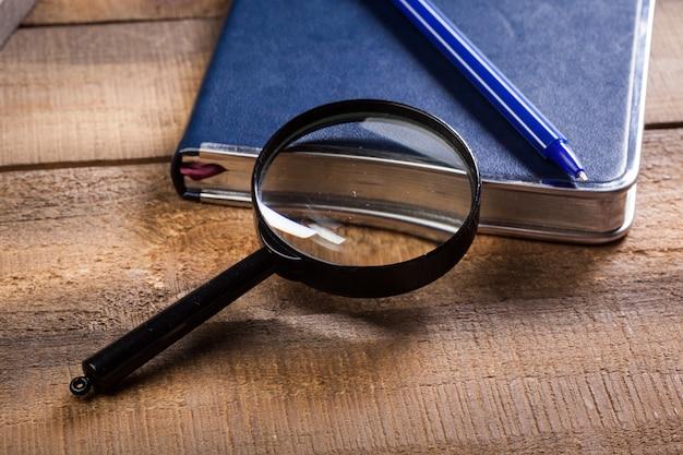 Vergrootglas en boek op het houten oppervlak