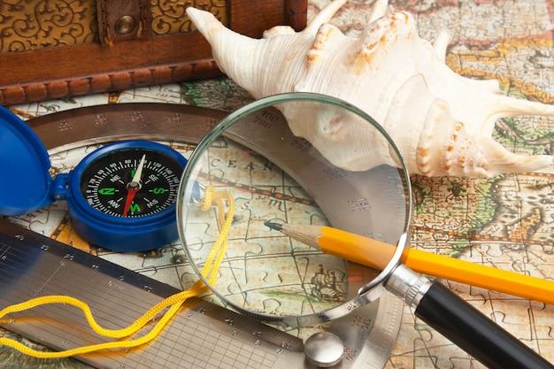 Vergrootglas en een kompas op de oude kaart