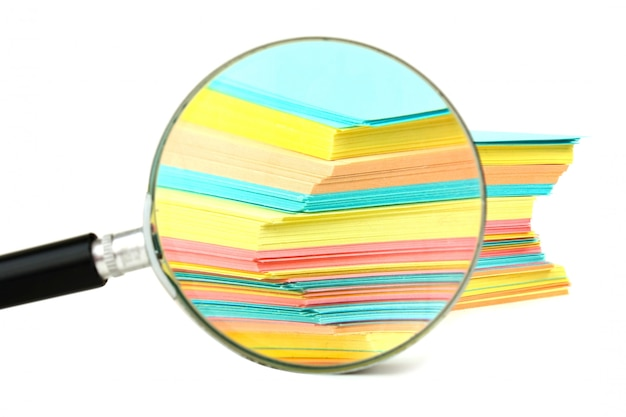 Vergrootglas en een stapel papier voor notities