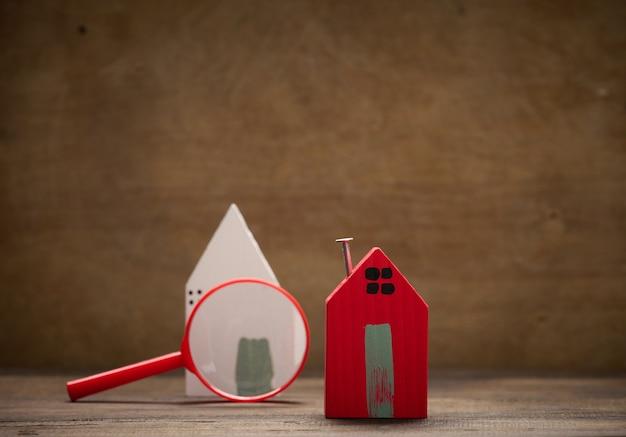 Vergrootglas en houten huis op een bruine achtergrond. vastgoed verhuur, aankoop en verkoop concept. makelaarsdiensten, reparatie en onderhoud van gebouwen