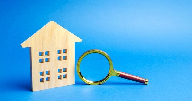 Vergrootglas en houten huis.
