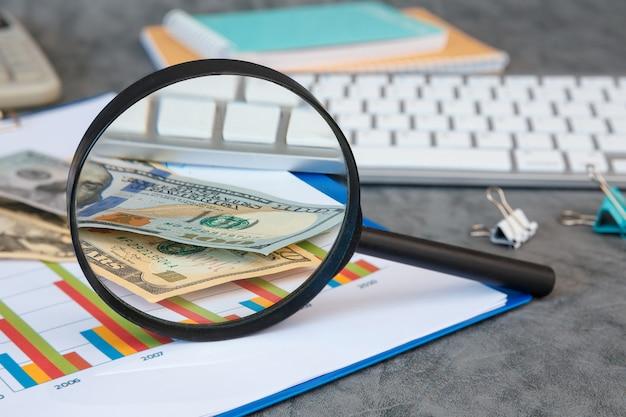 Vergrootglas en kantoorbenodigdheden, geld, documenten, toetsenbord op een grijze achtergrond.