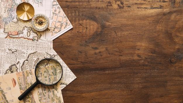 Vergrootglas en kompas op kaarten