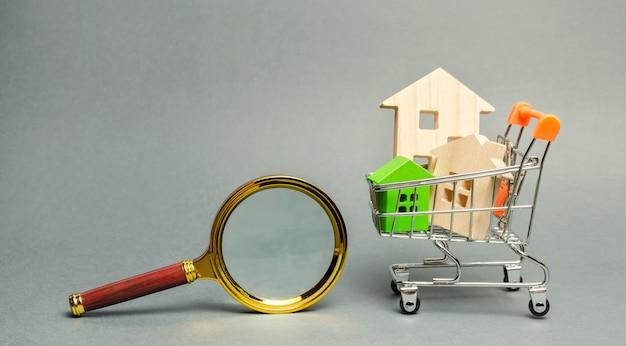 Vergrootglas en miniatuur houten huizen.