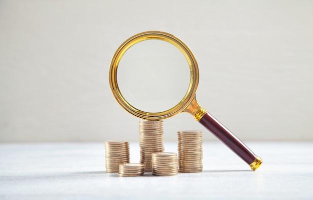 Vergrootglas en munten op het witte bureau.