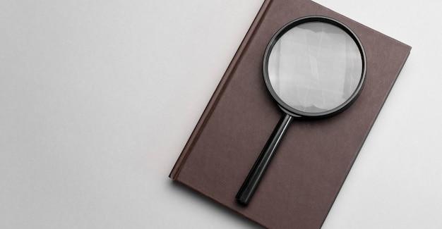 Vergrootglas en notitieboekje op grijze achtergrond.