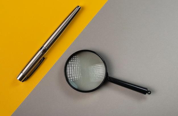 Vergrootglas en pen op grijze en gele tafel.