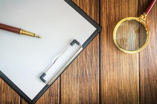 Vergrootglas en vel papier met lege takenlijst en pen
