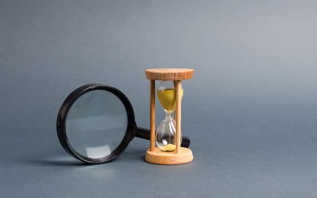 Vergrootglas en zandloper. zoek naar tijd