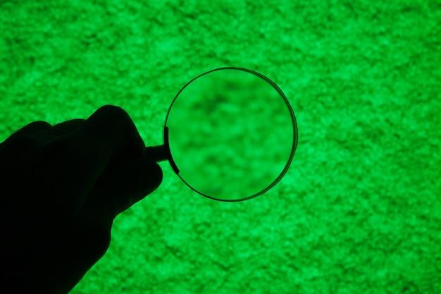 Vergrootglas kijkt naar een donkergroene substantie