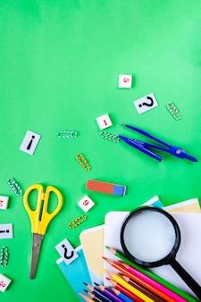 Vergrootglas, kleurpotloden, schaar, notitieboekjes op groen