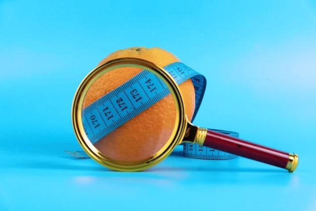 Vergrootglas, meetlint en sinaasappel op een blauwe achtergrond als symbool van cellulitis. anticellulitis programma concept.