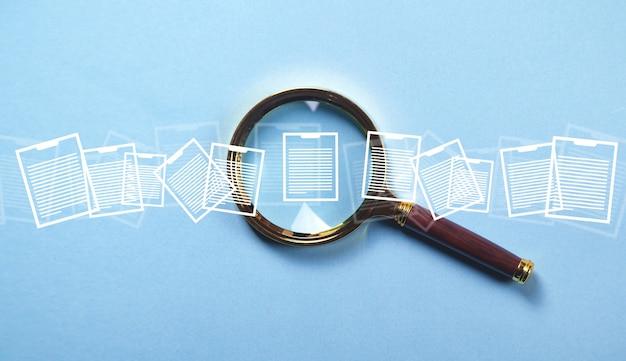 Vergrootglas met documenten op de blauwe achtergrond.
