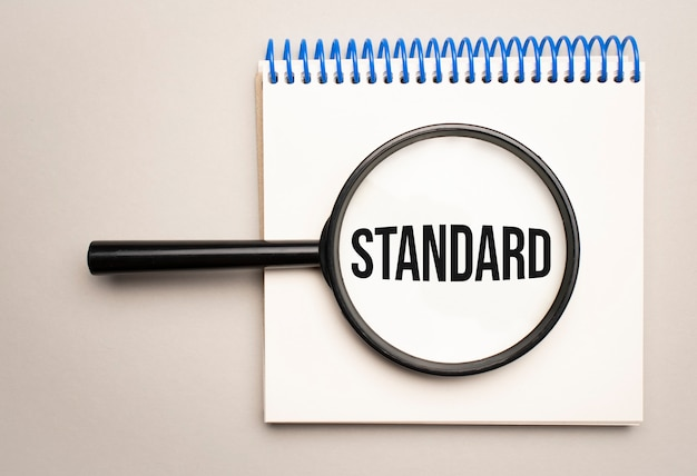 Vergrootglas met het woord standaard op de achtergrond van de grafiek