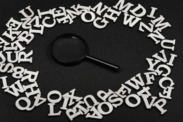 Vergrootglas omgeven door engelse letters op zwarte achtergrond
