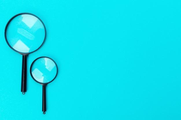 Vergrootglas op blauwe pastel achtergrond.