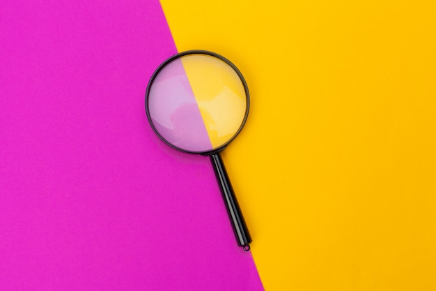 Vergrootglas op geel en roze