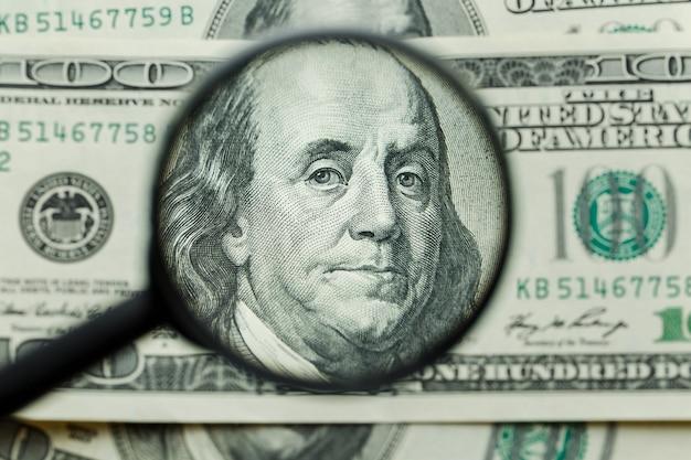 Vergrootglas op geldachtergrond