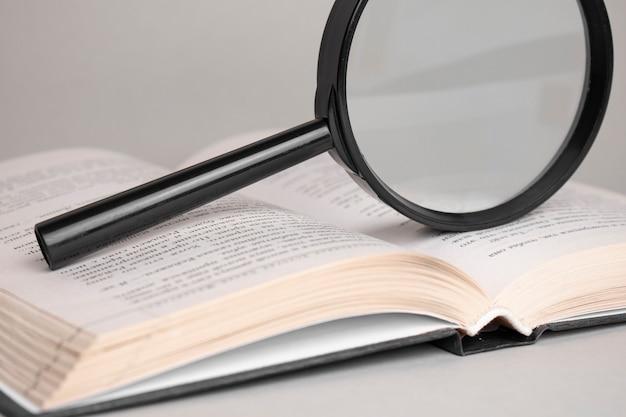 Vergrootglas op geopend oud boek voor zoeken en lezen concept