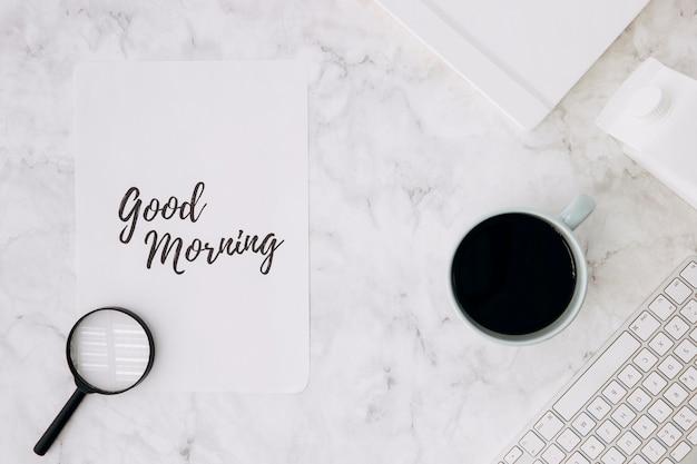 Vergrootglas op goedemorgen papier met koffiekopje; dagboek en toetsenbord op wit marmeren bureau