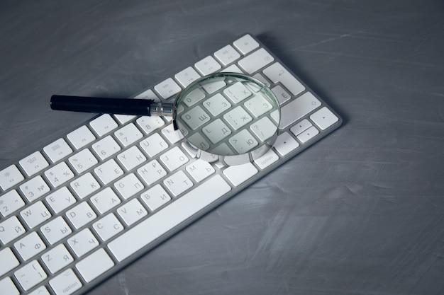 Vergrootglas op het computertoetsenbord op de tafel