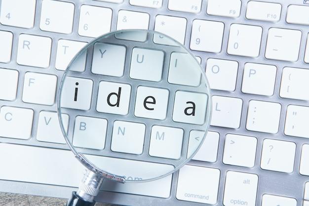 Vergrootglas op het toetsenbord. concept zoeken naar ideeën