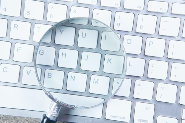 Vergrootglas op het toetsenbord. web zoekconcept