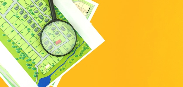 Vergrootglas op onroerendgoedkaart, huiszoekconcept, locatiekeuze voor de bouw van een gezinswoning, platliggend zakelijk kantoorbureaubladfoto