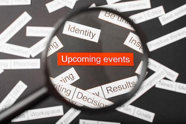 Vergrootglas over de rode inscriptie aankomende evenementen gesneden uit papier. omringd door andere inscripties op een donkere achtergrond. word cloud concept.