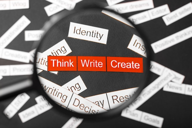 Vergrootglas over de rode inscriptie denk, schrijf, creëer uitgesneden papier. omringd door andere inscripties op een donkere achtergrond. word cloud concept.
