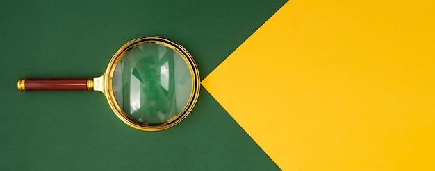 Vergrootglas over groene achtergrond met gele papieren straal met copyspace voor tekstbanner met gouden ...