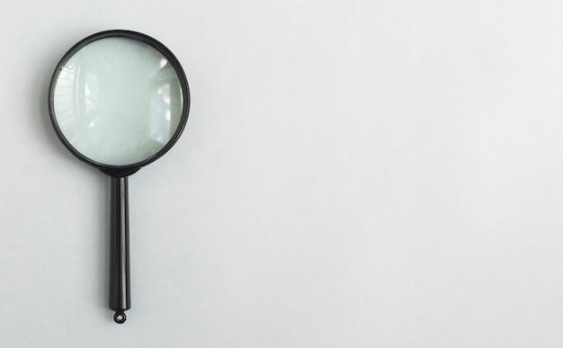 Vergrootglas over lichtblauwe grijze achtergrond met plaats voor tekstbanner met vergrootglas