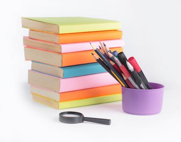 Vergrootglas, potloden en stapel boeken op witte achtergrond.