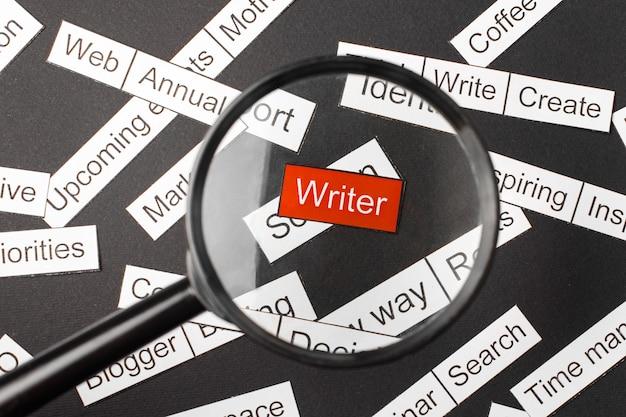 Vergrootglasglas over de rode inscriptieschrijver die uit papier is gesneden. omringd door andere inscripties op een donkere achtergrond. word cloud concept.