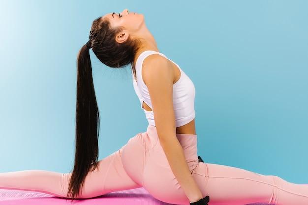 Vergrote foto. een sportief meisje met een mooi figuur touwt vast op een fitnessmat. blauwe achtergrond