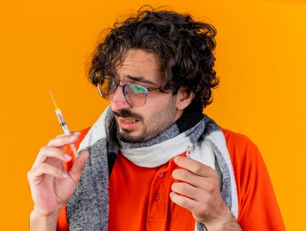Vergrote weergave van bang jonge zieke man met bril en sjaal met spuit en ampul kijken naar spuit geïsoleerd op oranje muur