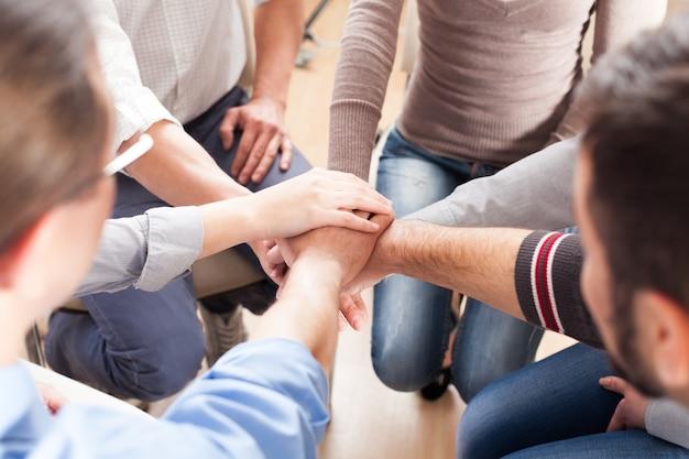 Vergrote weergave van een groep mensen die handen stapelen