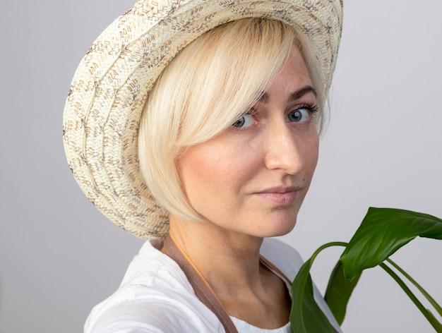 Vergrote weergave van een tevreden blonde tuinmanvrouw van middelbare leeftijd in uniform met een hoed die achter de plant staat in profielweergave
