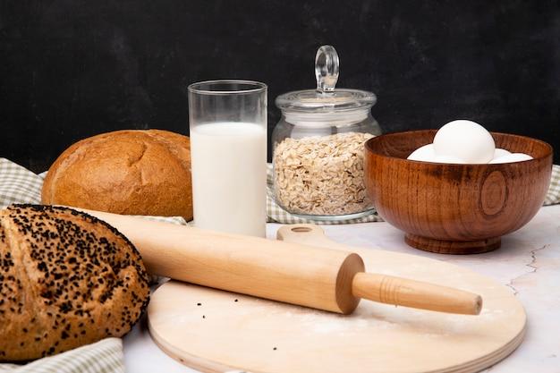 Vergrote weergave van glas melk en kom met eieren met brood havervlokken deegroller op snijplank op witte ondergrond en zwarte achtergrond