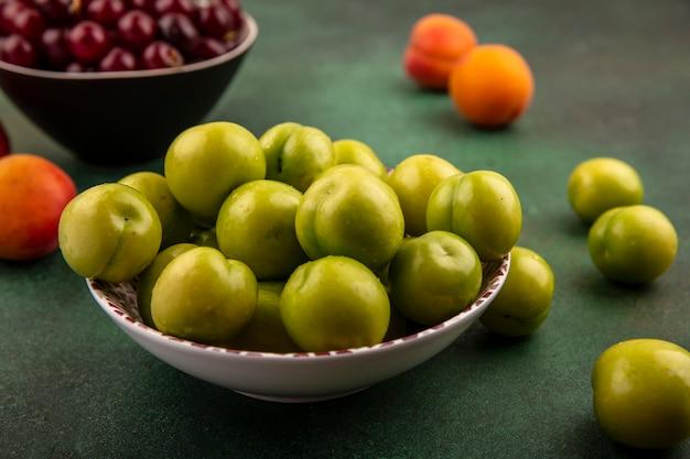 Vergrote weergave van groene pruimen in kom met kom kersen en abrikozen op groene achtergrond