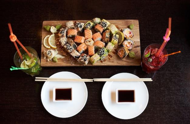 Vergrote weergave van heerlijke rollende sushi geserveerd op het houten bord met stokjes, sojasaus en cocktails