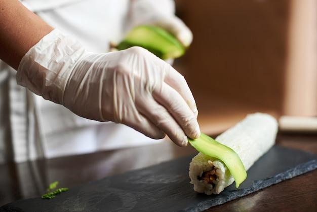 Vergrote weergave van het proces van het bereiden van rollende sushi op. hand in handschoen versiert rol met gesneden avocado
