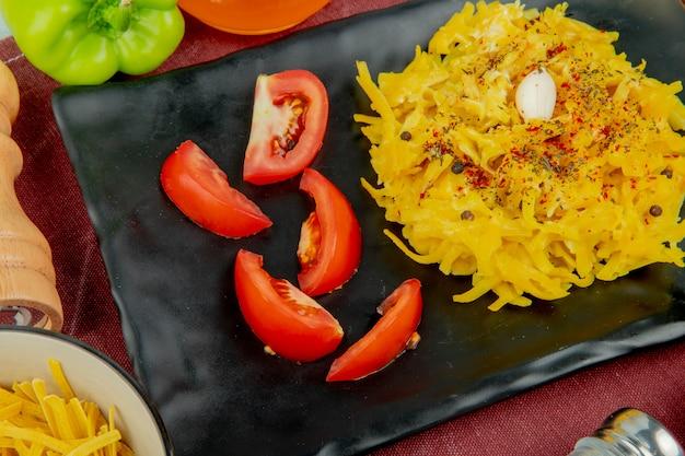 Vergrote weergave van macaroni pasta en gesneden tomaat in plaat met peper tagliatelle macaroni zout op bordo doek