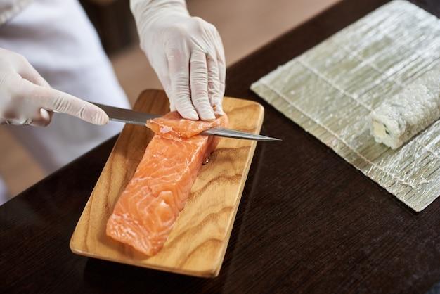Vergrote weergave van proces ter voorbereiding van heerlijke rollende sushi in restaurant. het wijfje dient wegwerphandschoenen in die zalm op houten raad snijdt.